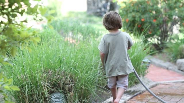 3 year old boy using garden hose