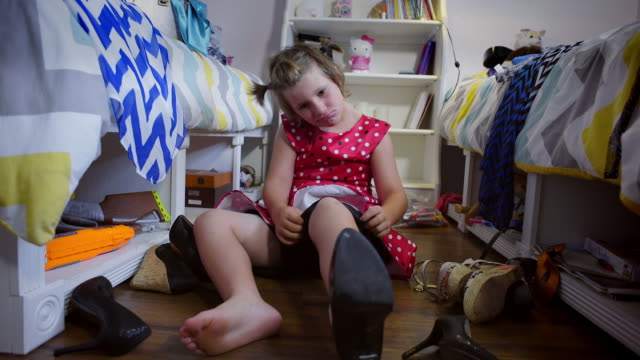 8 year old boy wearing make-up and red dress tries on high heel shoes