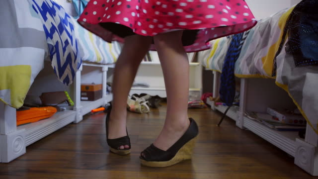 8 year old boy wearing make-up and red dress walks and spins on high heel shoes - Coverage on feet