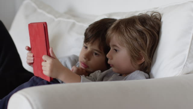 3 year old boy with his brother using a digital tablet - lettore di libri elettronici video stock e b–roll