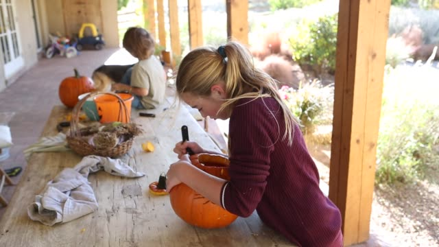 11 year old girl and her brother carving  pumpkins