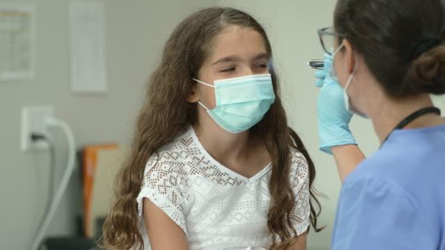 保護フェイスマスクを着用した医師の予約で12歳の女の子 - 小児科医点の映像素材/bロール