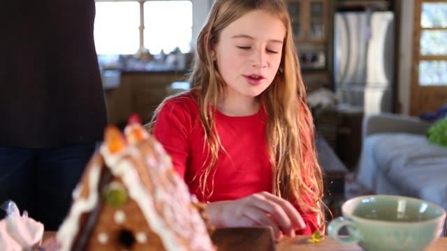 9 year old girl building a gingerbread house - ジェリービーンズ点の映像素材/bロール