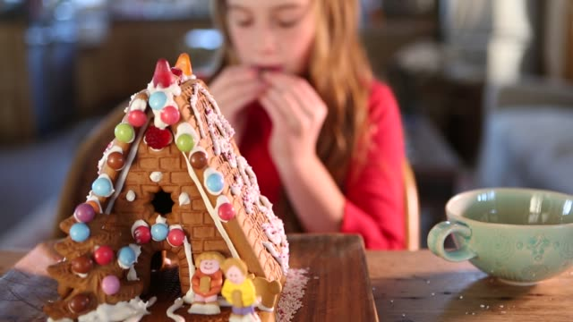 9 year old girl building a gingerbread house