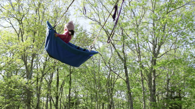 vidéos et rushes de 3 year old girl in boat shaped swing getting pushed in and out of tree filled sky - seulement des petites filles