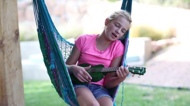 vídeos de stock, filmes e b-roll de 11 year old girl in hammock - short curto