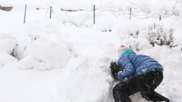 11 year old girl making a snowball