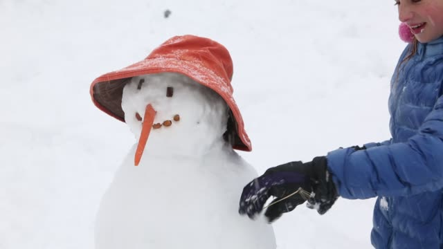 11 year old girl making a snowman - handschuh stock-videos und b-roll-filmmaterial