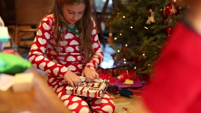 9 year old girl opening presents on Christmas morning