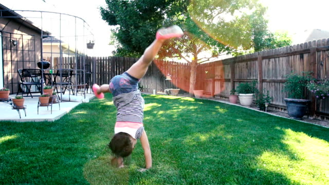 5 year old girl performing a cartwheel - cartwheel stock videos & royalty-free footage