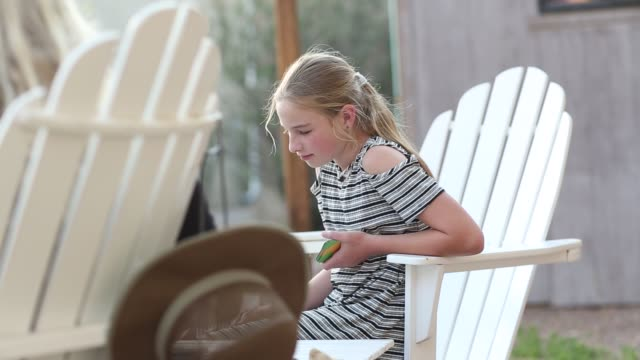 11 year old girl playing cards outdoors - 10歳から11歳点の映像素材/bロール