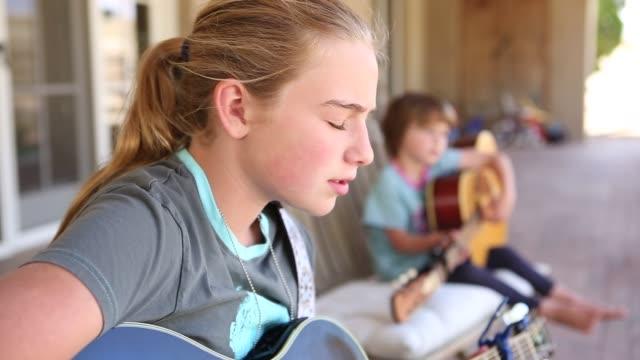 vídeos de stock, filmes e b-roll de 12 year old girl playing guitar - dedilhando instrumento
