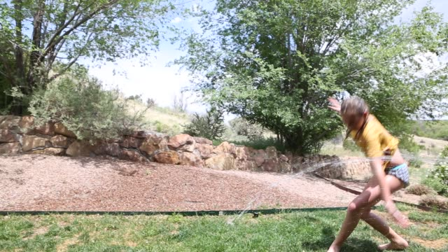 11 year old girl playing in sprinkler