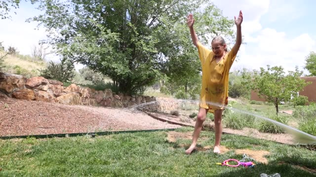 11 year old girl playing in sprinkler - 10 seconds or greater stock videos & royalty-free footage