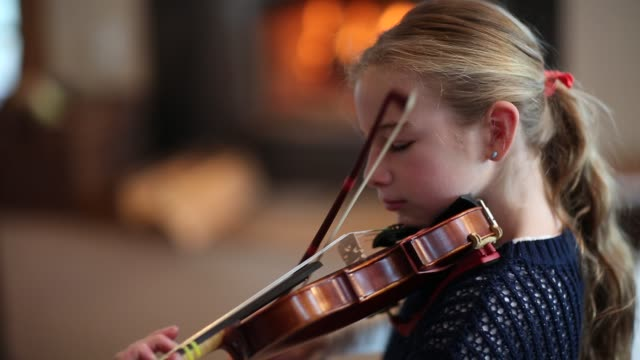 vídeos de stock e filmes b-roll de 8 year old girl playing violin close to a fireplace at home. - violino