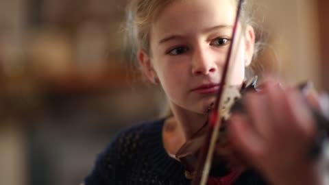 8 year old girl playing violin close to a fireplace at home. - musikinstrument bildbanksvideor och videomaterial från bakom kulisserna