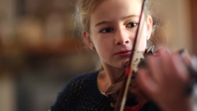 8 year old girl playing violin close to a fireplace at home.