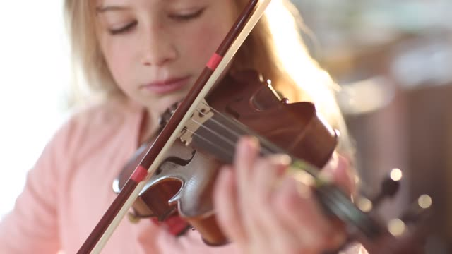 8 year old girl playing violin close to a fireplace at home - practicing stock videos & royalty-free footage