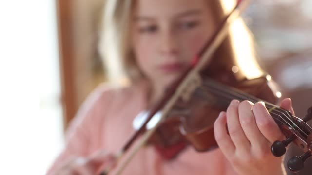 vídeos de stock, filmes e b-roll de 8 year old girl playing violin close to a fireplace at home - violino