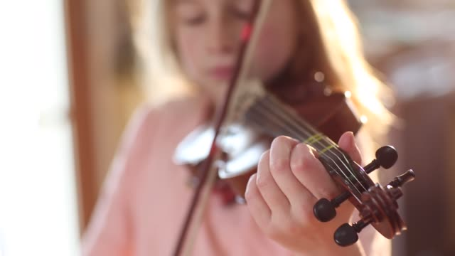 vídeos de stock e filmes b-roll de 8 year old girl playing violin close to a fireplace at home - violino