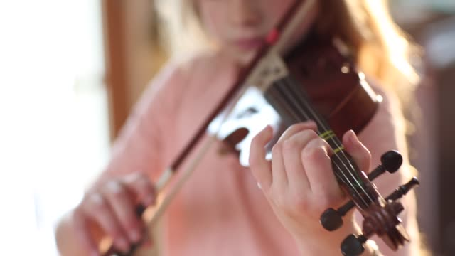 8 year old girl playing violin close to a fireplace at home