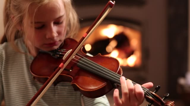 8 year old girl playing violin in front of fireplace - violin stock videos & royalty-free footage