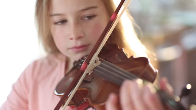 8 year old girl playing violin in front of fireplace