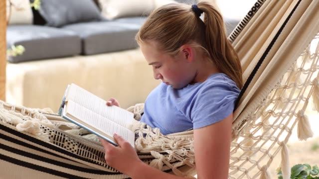 vídeos de stock, filmes e b-roll de 12 year old girl reading book in hammock - old book