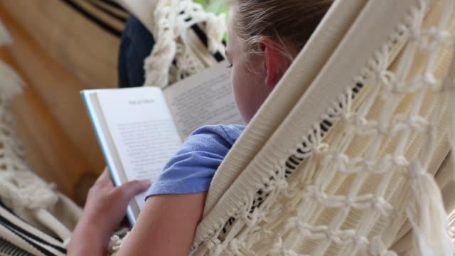12 year old girl reading book in hammock - ハンモック点の映像素材/bロール