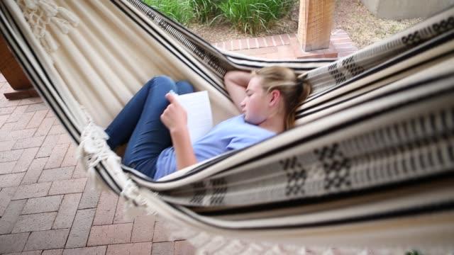 12 year old girl reading book in hammock