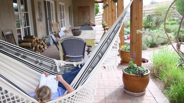 12 year old girl reading book in hammock - lamy new mexico stock videos and b-roll footage