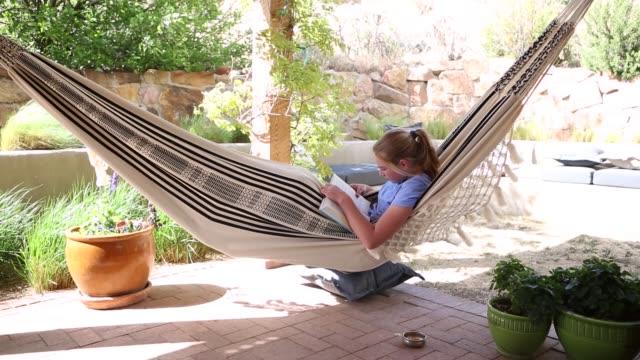 12 year old girl reading in hammock - hammock stock videos & royalty-free footage