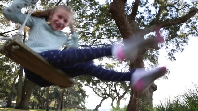 8 year old girl spinning on a swing in the marsh low country - south america stock videos & royalty-free footage