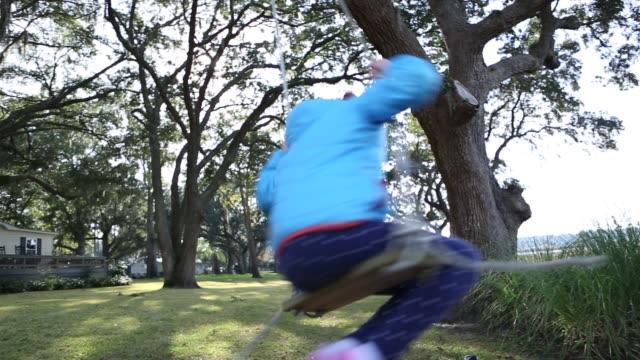 stockvideo's en b-roll-footage met 8 year old girl spinning on a swing in the marsh low country - haar naar achteren