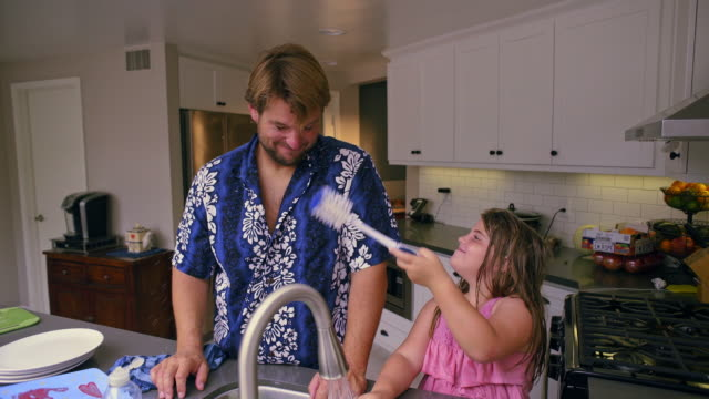 8 year old girl splashes her dad while they clean dishes together.