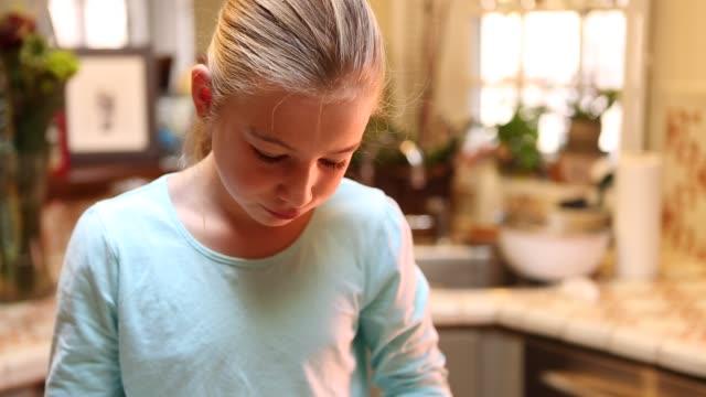 vídeos de stock e filmes b-roll de 9 year old girl stirring batter in the kitchen - concha utensílio de servir