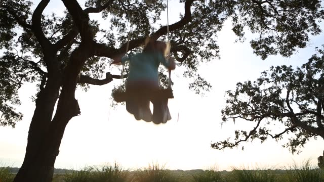 8 year old girl swinging on a swing in the marsh low country - south america stock videos & royalty-free footage