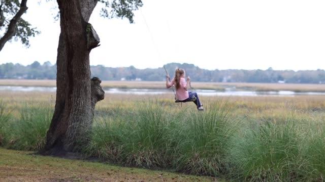 stockvideo's en b-roll-footage met 8 year old girl swinging on a swing in the marsh low country - haar naar achteren