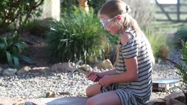 11 year old girl using hammer outside