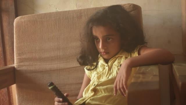 テレビを見て5歳の女の子 - テレビのリモコン点の映像素材/bロール