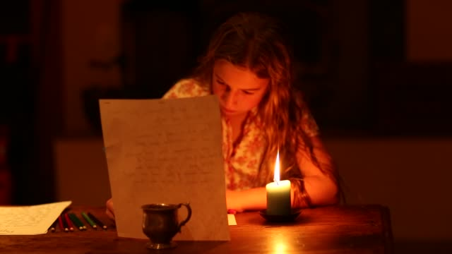 9 year old girl writing by candle light at home