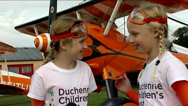9 year old girls wing walk for charity shots of rose climbing onto plane with the help of a professional rose strapped into seat putting on goggles... - superwoman stock videos and b-roll footage