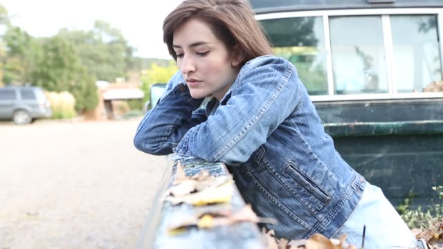 vídeos de stock, filmes e b-roll de 26 year old hispanic woman sitting in bed of old pick up truck - jaqueta jeans