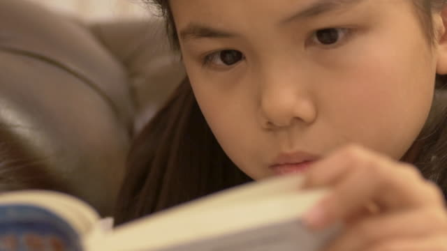 10 year old Japanese girl concentrate reads a book