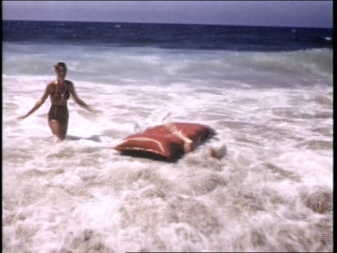 15 year old Marilyn Monroe wearing red bikini playing with other young girls in the ocean surf / they cling to an inflatable raft and sit on it 15...