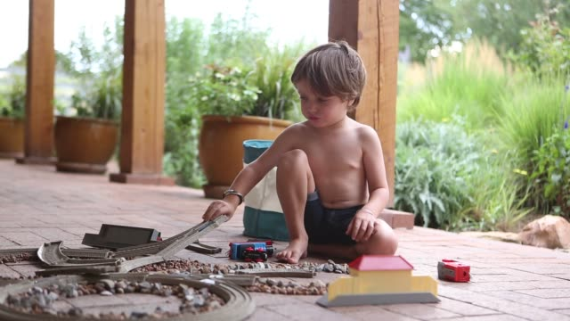 stockvideo's en b-roll-footage met 4 year old  playing with train set under portal - in kleermakerszit