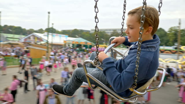 "10 year old school boy takes a chain swing ride while visiting the ""oide wiesn"" during oktoberfest 2017 - happy child - 回転遊具点の映像素材/bロール"