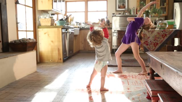 stockvideo's en b-roll-footage met 8 year old sister dancing in front of her 15 month old brother - keuken huis