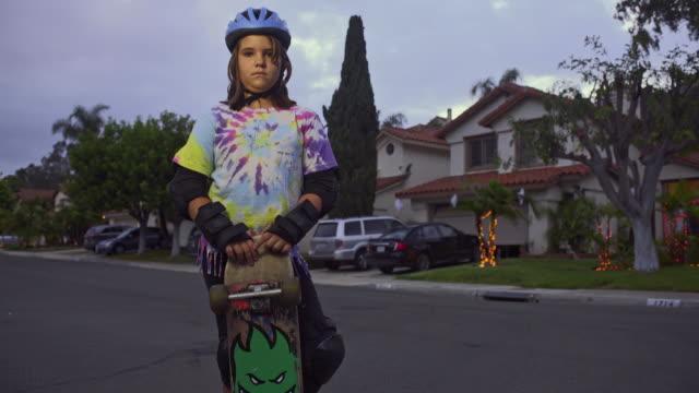 vidéos et rushes de 10 year old skater girl with skateboard on neighborhood street at dusk. wide, tilt up, jib. - trans