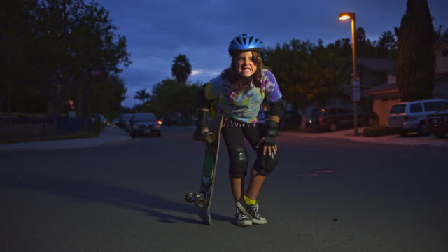 10 year old skater girl with skateboard on neighborhood street at dusk laughing and Making faces. Wide.